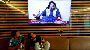 Iraqi youth watch the news of IS group leader Abu Bakr al-Baghdadi death in Najaf, Iraq, on October 27, 2019.