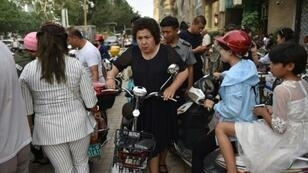 "UN ambassadors from 37 countries have released a letter defending China's treatment of Uighur and other minorities in the Xinjiang region, in direct response to Western criticism This photo taken on June 4, 2019 shows a Uighur woman pushing an electric bicycle in a crowded street in Kashgar, and more than one million ethnic Uighurs and other mostly Muslim minorities are believed to be held in internment camps that Beijing describes as ""vocational education centres"" aimed at steering people away from religious extremism"