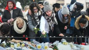 Des personnes allument des bougies et déposent des fleurs autour d'un mémorial improvisé à Strasbourg le 16 décembre 2018.