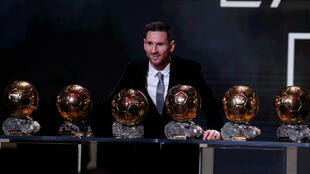 Lionel Messi poses along with his six Ballons d'Or trophies.