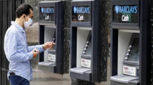 Un cliente con mascarilla se dispone a usar un cajero automático en el exterior de una sucursal del Barclays, el 29 de julio de 2020 en el centro de Londres