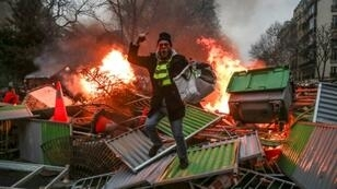 """A yellow vest """"Gilets Jaunes"""" anti-government protestor stands on a burning barricade in Paris on January 5 during clashes with security personnel"""