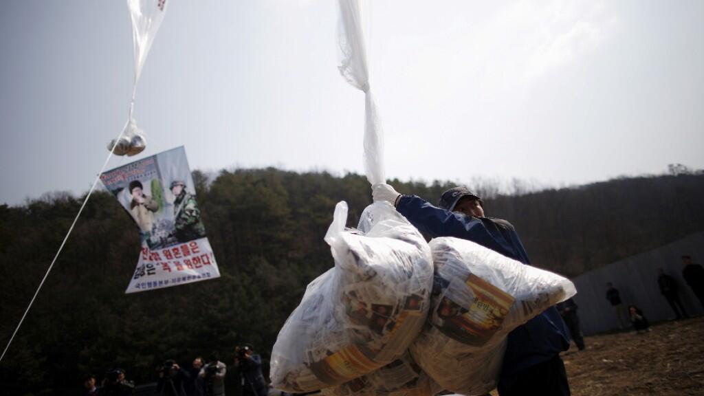 Park Sang-Hak, un desertor norcoreano que vive en el Sur y líder de un grupo cívico anti-Corea del Norte, sostiene un globo con panfletos que denuncian al líder norcoreano Kim Jong Un, cerca de la zona desmilitarizada que separa las dos Coreas en Paju, Corea del Sur, 26 de marzo de 2016.
