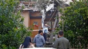 شرطي يتفحص المنزل الذي تضرر جراء سقوط صاروخ عليه في ميشميريت شمال تل أبيب بتاريخ 25 آذار/مارس 2019