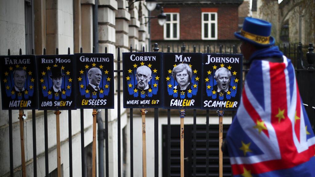 Un manifestante anti-Brexit pasa frente a unas señales de protesta en Londres, Reino Unido, el 2 de abril de 2019.