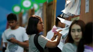 Una mujer mira la lista de candidatos a las elecciones tailandesas en un colegio electoral en Bangkok, Tailandia, el 17 de marzo de 2019.