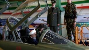 """روحاني جالسا في قمرة قيادة المقاتلة """"كوثر"""" خلال معرض الصناعات الدفاعية في طهران."""