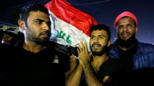 Des hommes portent le cercueil d'un manifestant tué à Bagdad, en Irak, le 25octobre2019.