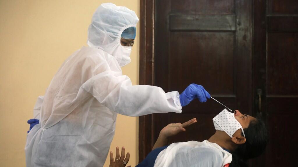 Personal sanitario indio realiza una prueba PCR nasal para detectar coronavirus a un ciudadano en Mumbai, India, el 12 de septiembre de 2020.