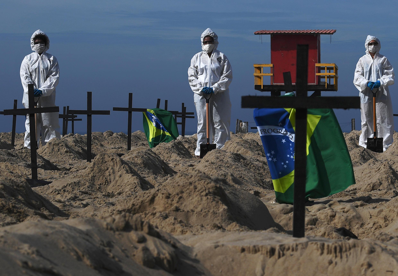 Cent tombes creusées symboliquement sur la plage de Copacabana, à Rio de Janeiro, pour rendre hommage aux milliers de Brésiliens morts du Covid-19, le 11 juin 2020.