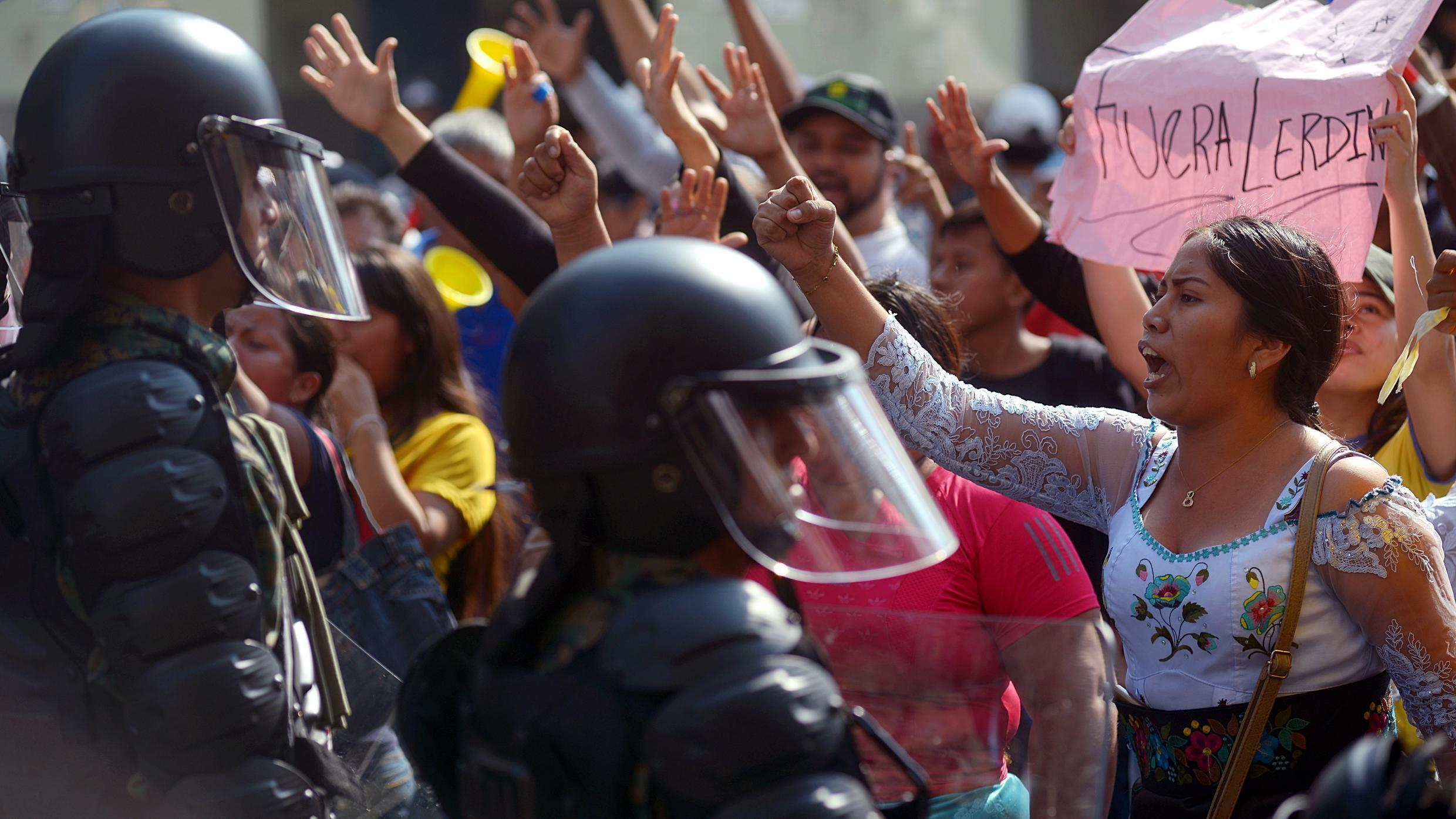 People protest against a fuel price hike ordered by the government to secure an IMF loan in front of riot police in Guayaquil, Ecuador on October 9, 2019.