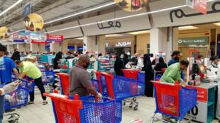 Los clientes hacen cola en un supermercado durante un toque de queda para frenar la propagación del coronavirus, el 3 de abril de 2020 en Riad