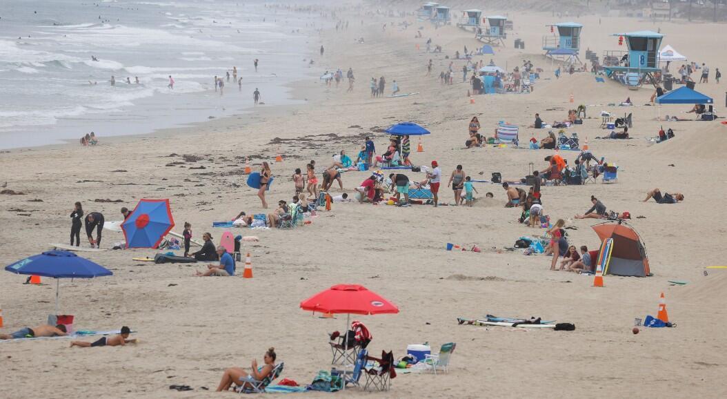 Cientos de personas disfrutan de la playa cuando Estados Unidos pasó el jueves un total de más de 4 millones de infecciones por coronavirus. En Huntington Beach, California, EE. UU., el 23 de julio de 2020.