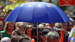 Un hombre lleva un paraguas con la bandera de la Unión Europea durante una manifestación para reivindicar la unidad de Europa y en contra del nacionalismo en todo el bloque. Viena, Austria, 19 de mayo de 2019.