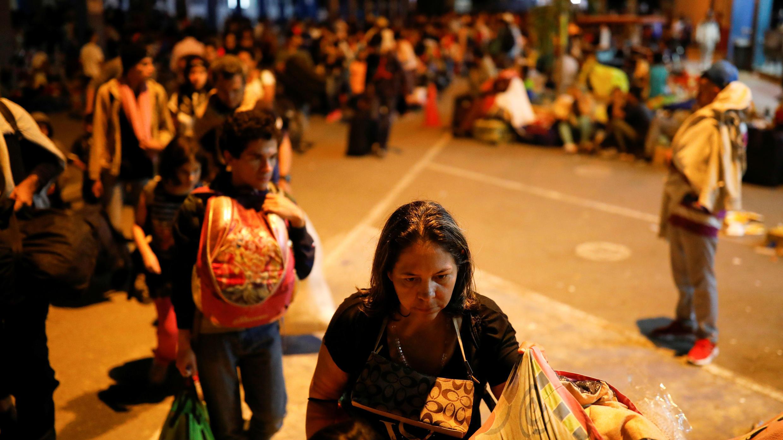 Migrantes venezolanos hacen fila en un centro de servicio fronterizo entre Ecuador y Perú, para procesar sus documentos y poder continuar su viaje, en Tumbes, Perú, el 15 de junio de 2019.