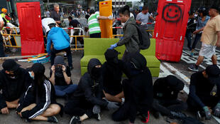 Anti-government protesters sit as local residents remove a barricade outside the University of Hong Kong, in Hong Kong, China, November 16, 2019.
