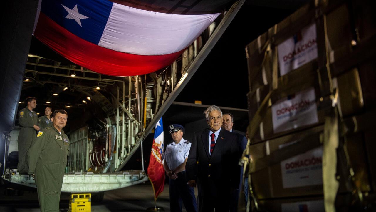 Sebastián Piñera, junto al ministro de Relaciones Exteriores de Chile, Roberto Ampuero, inspecciona un avión de la Fuerza Aérea de Chile con ayuda humanitaria para Venezuela en Santiago, Chile, el 21 de febrero de 2019.