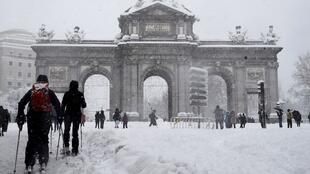 Varias personas caminan junto a la Puerta de Alcalá de Madrid cubierta de nieve