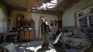 أرام فاردازاريان يقف داخل منزله الذي طاله القصف في 18 تموز/يوليو 2020 في قرية أيغيبار في منطقة تافوش خلال معارك مع أذربيجان