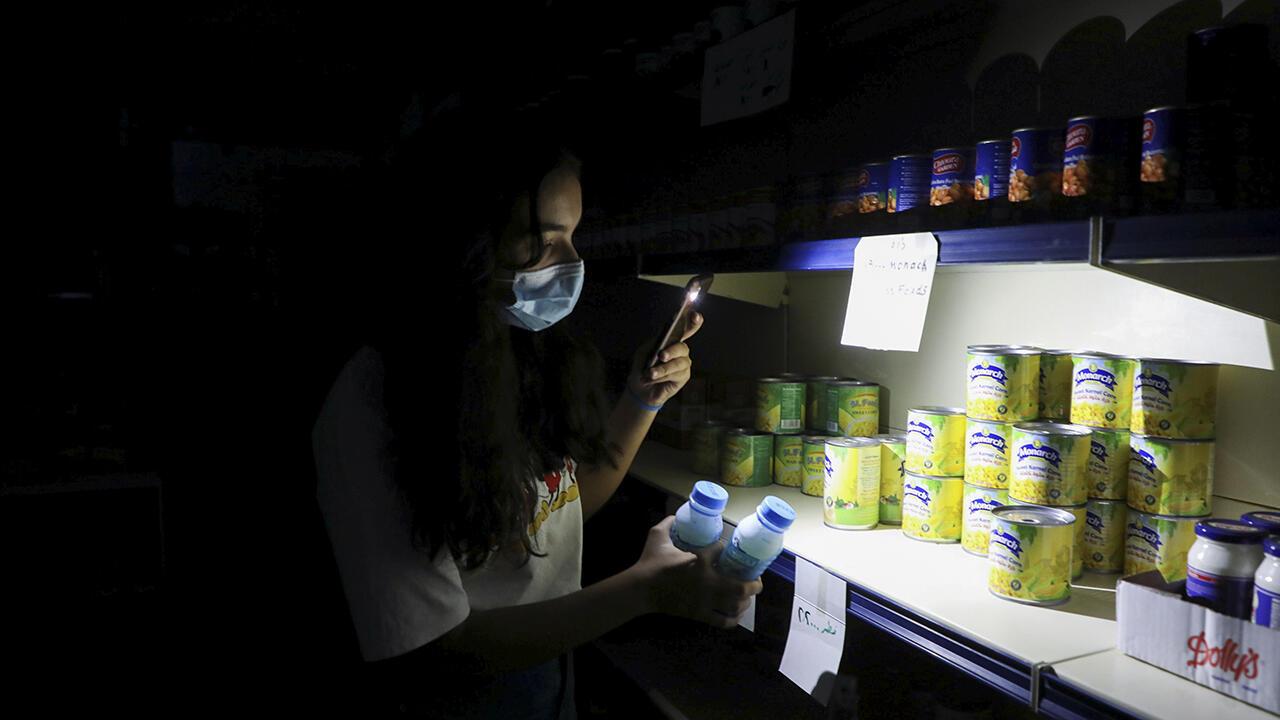 Una ciudadana utiliza la luz de su teléfono para poder iluminarse en un mercado ubicado en el sur de Bhamdoun en medio del apagón, en Líbano, el 9 de octubre de 2021.