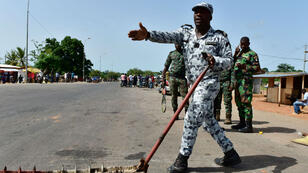 Un policier ivoirien fait la circulation à l'entrée de Bouaké, à proximité de soldats mutins, le 16 mai 2017.