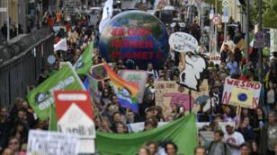 """Des personnes défilent et portent un globe sur lequel on peut lire """"Il n'y a pas de planète B"""" à Berlin, le 20 septembre 2019."""