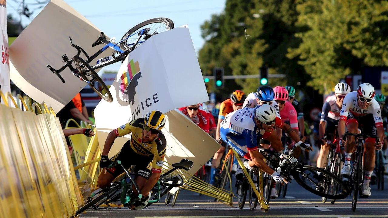 A la izquierda, y de amarillo, Dylan Groenewegen, corredor del Jumbo-Visma, al cierre de la primera etapa del Tour de Polonia y luego de empujar hacia un costado a Fabio Jakobsen. De este último solo se ve su bicicleta (en el aire, encima de Groenewegen) y un brazo en medio de las barreras de contención. Kilómetro 195 entre Chorzow y Katowice, Polonia, 5 de agosto de 2020.