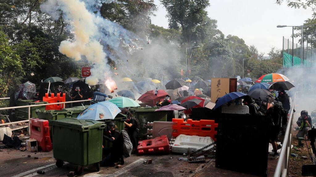 Estudiantes universitarios se refugian mientras se enfrentan con la policía antidisturbios en la Universidad China de Hong Kong.