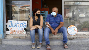 "Israeli Naama Goldman-Shwartz, 45, (L) and Arab Ahmad ""Juha"" Jorban sit at the entrance of Juha's Guesthouse that they run together"