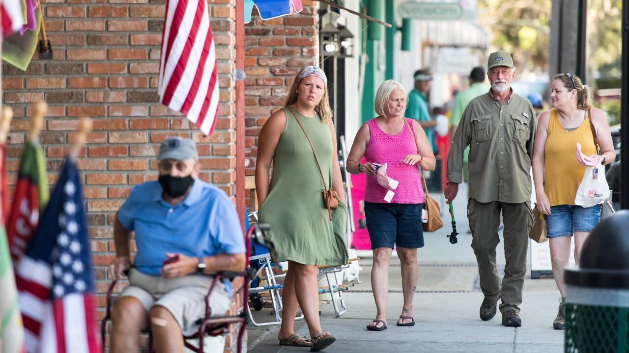 Grupos de personas caminan por una calle de St. Simmons Island, Georgia, una semana después de que el gobernador del estado, Brian Kemp, emitiera una orden con la que prohíbe a las autoridades municipales hacer obligatorio el uso de las mascarillas, en medio de la pandemia del Covid-19. En Georgia, Estados Unidos, el 17 de julio de 2020.