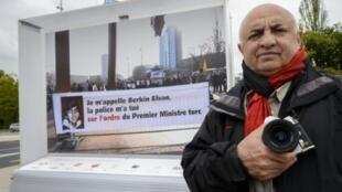 المصور دمير سونميز أمام لافتة تحمل صورة الفتى بركين الوان