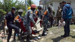 Forces de police népalaises qui dégagent un corps des décombres à Katmandou, au Népal, le 27 avril 2015.