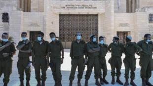 جنود إسرائيليون يقفون خارج الكنيس اليهودي الكبير المغلق منذ بدء انتشار فيروس كورونا ويضعون الكمامات الواقية من الفيروس في 15 أيلول/سبتمبر 2020