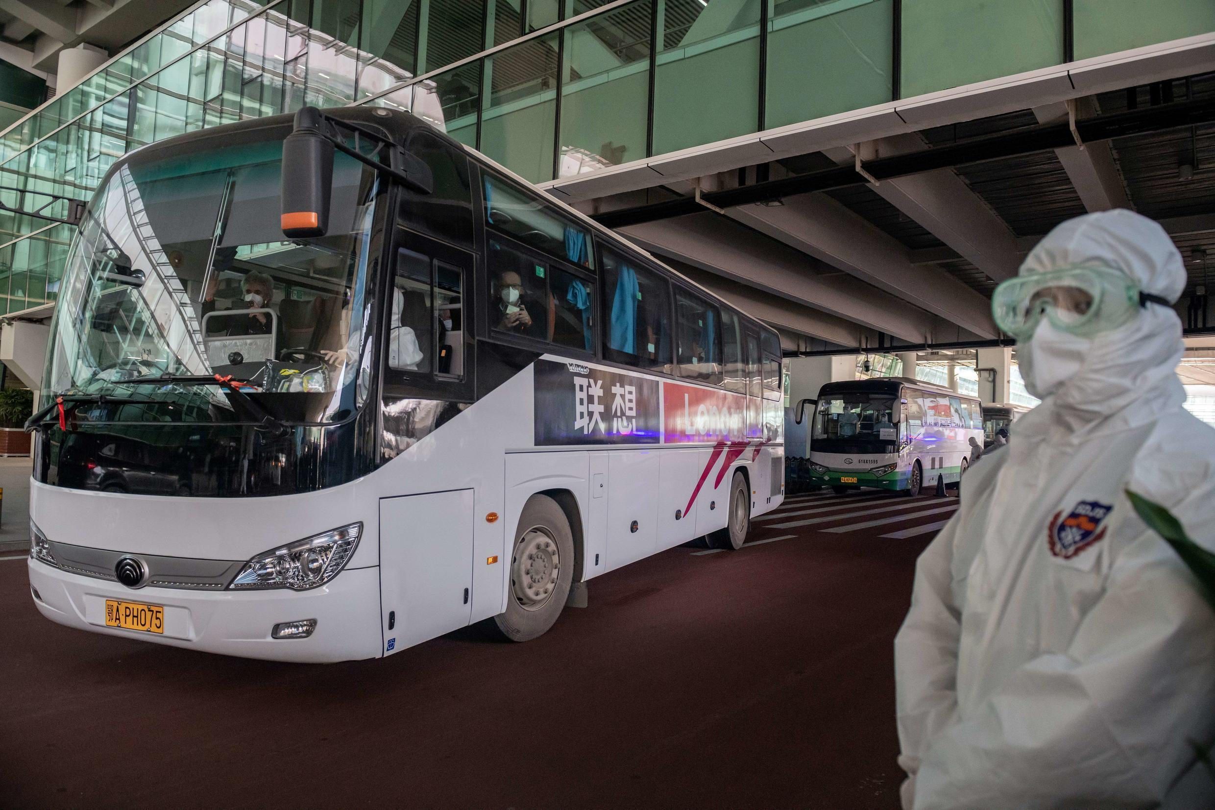 A bus carrying experts from a World Health Organization team that came to China to investigate the origins of the coronavirus leaves the airport after its arrival in Wuhan on January 14, 2021.