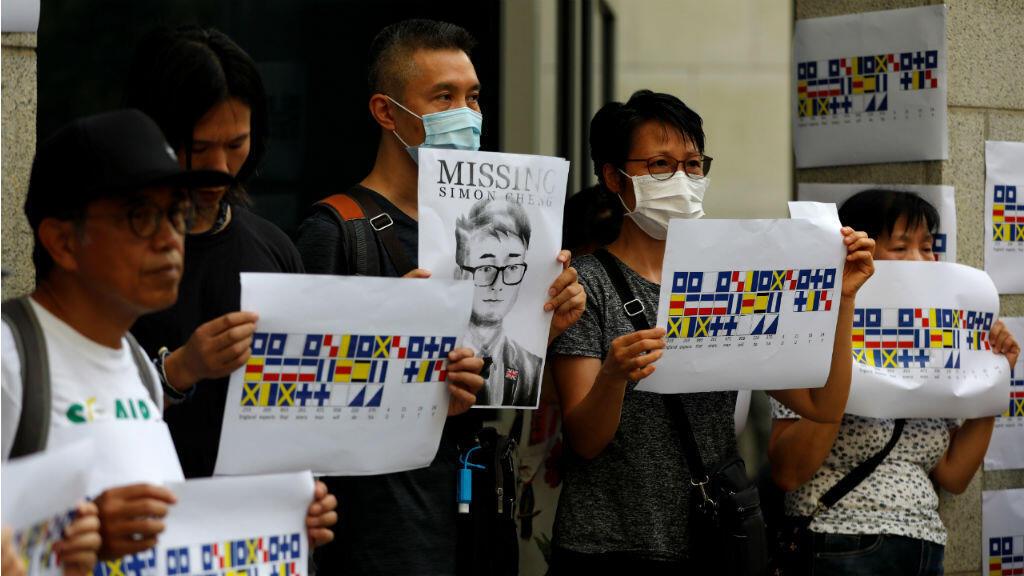 Manifestantes sostienen carteles con la foto de Simon Cheng, un miembro del personal del consulado británico que desapareció el 9 de agosto.El 21 de agosto de 2019.