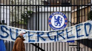 """Un piéton passe devant une banderole dénonçant la """"super avidité"""" du projet d'une Super Ligue européenne privée en concurrence frontale avec la Ligue des Champions, le 20 avril 2021 devant les grilles d'une entrée du stade de Stamford Bridge à Chelsea, avant le match de Premier League contre Brighton"""