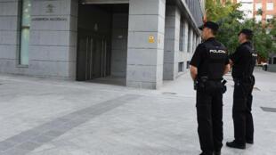 Deux policiers devant l'Audience nationale d'Espagne, à Madrid, où les suspects des attentats de Catalogne ont comparu.
