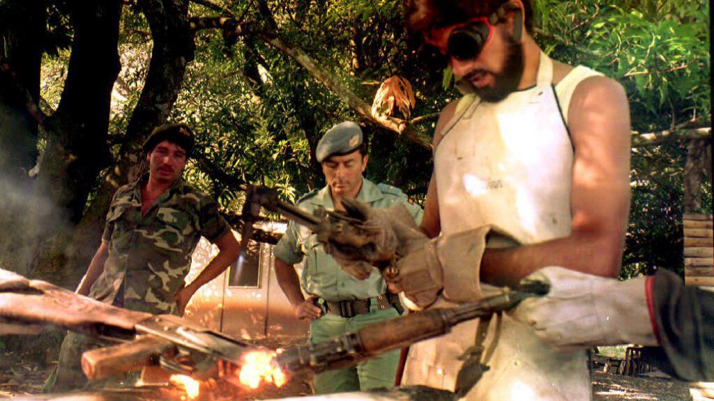 Los miembros del Frente Farabundo Martí de Liberación Nacional (FMLN) destruyen un rifle el 14 de diciembre de 1992 bajo la supervisión de un miembro del equipo de Observadores de las Naciones Unidas, de conformidad con El acuerdo de paz del 16 de enero de 1992.