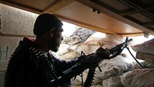 A Syrian rebel fighter from the National Liberation Front (NLF) mans a position in Rashidin in Aleppo province on November 26, 2018