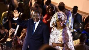 Le Président du Sénégal, Macky Sall, et son épouse, Marieme Faye Sall, saluent les spectateurs, le 1er décembre 2018, lors de la cérémonie pour sa désignation en tant que candidat à la prochaine élection présidentielle.