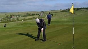 Deux joueurs de golf sont les premiers à revenir au  Dyke Golf Club, sur la côte Sud de l'Angleterre, qui rouvre à la faveur d'un assouplissement des mesures contre le coronavirus, le 13 mai 2020