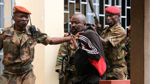 """In this file photo taken on October 29, 2018 members of the armed forces arrest Central African MP Alfred Yekatom aka """"Rambo"""" (C), who represents the southern M'baiki district former militia leader, after he fired the gun at the parliament in Bangui. Central African MP Alfred Yekatom aka """"Rambo"""" was extradited on November 17, 2018 to The Hague, The Netherlands, after an arrest warrant was issued by the International Criminal Court."""