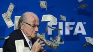 De faux dollars tombent sur Sepp Blatter lors d'une conférence de presse de la Fifa, le 20 juillet 2015 à Zurich.