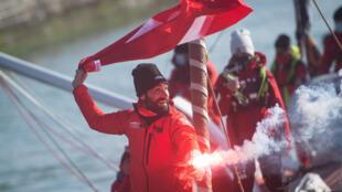 """Le skipper suisse Alan Roura, heureux à bord de son monocoque """"La Fabrique"""", après avoir franchi la ligne d'arrivée du Vendée Globe, le 12 février 2021 au large des Sables-d'Olonne"""