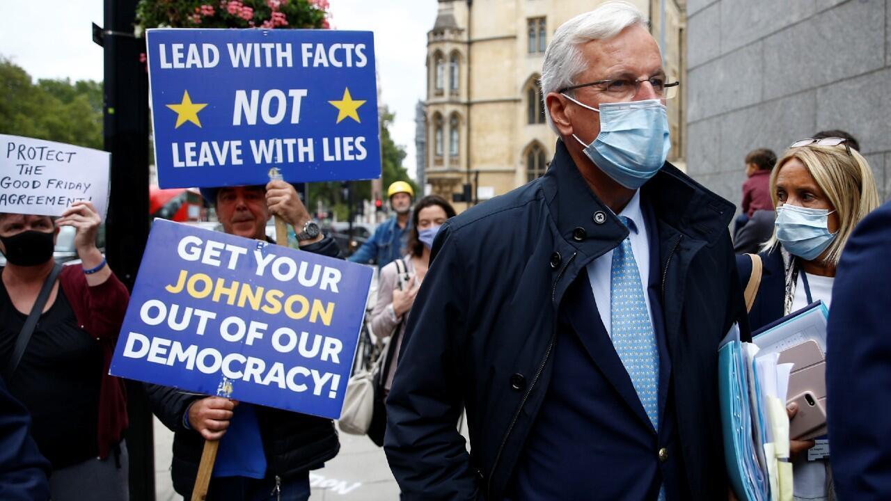 El manifestante anti-Brexit Steve Bray sostiene pancartas mientras el negociador jefe de la UE, Michel Barnier, camina con un séquito a una reunión en Westminster, Londres, Reino Unido, el 9 de septiembre de 2020.
