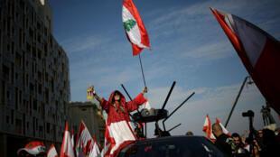 Une manifestante brandit un drapeau libanais devant des officiers de police, au cours d'une manifestation anti-gouvernementale à Beyrouth, au Liban, le 11 novembre 2019.