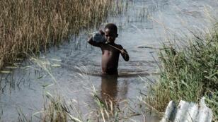 صبي يمشي وسط مياه الفيضانات التي خلفها إعصار إيداي، في بيرا، موزمبيق، في 27 مارس آذار 2019