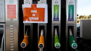 """Un letrero que dice """"Fuera de servicio"""" cuelga de las bombas de combustible en una estación de servicio durante una huelga de combustible, cerca de Lisboa, Portugal , el 12 de agosto de 2019."""