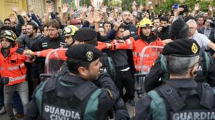 Des pompiers tentent de contenir un groupe d'électeurs face à la Garde civile à l'extérieur d'un bureau de vote à San Julia de Ramis, le 1er octobre.