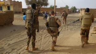 Des soldats de la Force Barkhane et de l'armée malienne circulent dans la ville de Menaka, dans l'est du Mali, lors d'une patrouille, le 21 mars 2019.